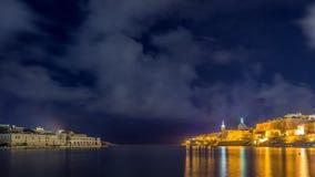 瓦莱塔,马耳他-有从Ta ` xbiex采取的StPauls大教堂的瓦莱塔和马努埃尔海岛老城市的地平线视图在夜之前 库存照片