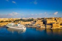 瓦莱塔,马耳他-游轮在日出的盛大港口与瓦莱塔古城 免版税库存图片