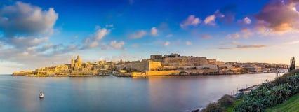 瓦莱塔,马耳他-瓦莱塔和斯利马古城的全景地平线视图日出的从马努埃尔海岛射击了在春天 库存图片
