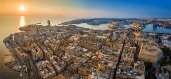 瓦莱塔,马耳他-瓦莱塔空中全景地平线视图日出的与输入在盛大港口的游轮 免版税库存照片