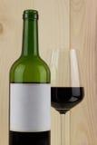 瓶与一块精采玻璃的红葡萄酒在木背景 免版税库存照片