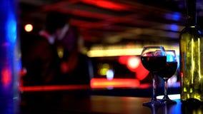 瓶与两块玻璃的酒,亲吻在被弄脏的背景的年轻夫妇 免版税库存照片