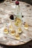 瓶与小玻璃的李子白兰地酒在木桌上 图库摄影
