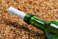 瓶与帮助消息的酒在海滩的沙子在太阳夏天 免版税库存照片