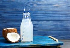 瓶与新鲜的坚果的椰子水 库存照片
