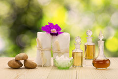 瓶与桃红色兰花、石头和白色毛巾的芳香油在被弄脏的绿色bokeh背景的葡萄酒木地板上 免版税库存图片