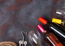 瓶与玻璃和拔塞螺旋开启者的红色白色和桃红色玫瑰酒红色在石厨房用桌背景 顶视图 t的空间 库存照片