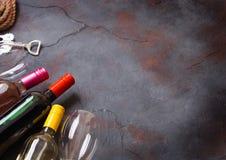 瓶与玻璃和拔塞螺旋开启者的红色白色和桃红色玫瑰酒红色在石厨房用桌背景 顶视图 t的空间 免版税库存图片