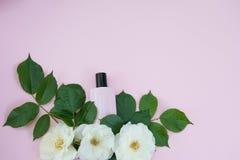 瓶与白花的女性化妆用品在粉色背景,拷贝空间 免版税库存图片