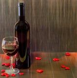 瓶与透明玻璃的酒用红葡萄酒,纺织品红色心脏,木纹理背景,关闭 免版税库存图片