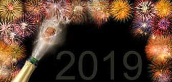 瓶与飞行黄柏的在西尔维斯特的香槟和烟花2019年 免版税库存照片