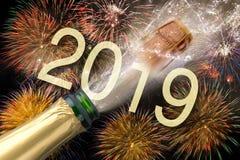 瓶与飞行黄柏的在西尔维斯特的香槟和烟花2019年 库存图片