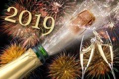 瓶与飞行黄柏的在西尔维斯特的香槟和烟花2019年 免版税库存图片