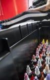 瓶五颜六色的纹身花刺墨水,在有服装的纹身花刺客厅里 免版税库存图片