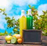 瓶从柑橘水果和黑板的汁液 免版税库存图片