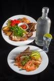 瓶伏特加酒和玻璃用开胃菜 免版税库存照片