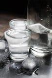 瓶伏特加酒特写镜头视图与站立在冰黑色的玻璃的 免版税库存照片