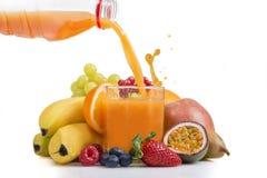从瓶倾吐的多维生素果汁 免版税库存图片