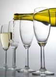 瓶倾吐的白葡萄酒葡萄酒杯 库存图片