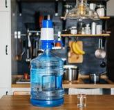 瓶净水与蓝色盛况的19公升在厨房的背景的公寓内部 清洗和健康 免版税库存照片