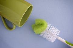 洗瓶刷和绿色杯子 免版税库存照片