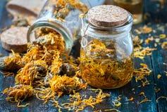 瓶和干金盏草officinalis瓣有被浸软的油的在木背景 免版税库存照片
