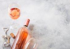 瓶和杯与黄柏和拔塞螺旋开启者的桃红色玫瑰酒红色在石厨房用桌背景 顶视图 文本的空间 免版税库存照片