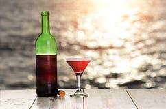 瓶和杯在亚麻制桌上的红葡萄酒反对海或海洋日落的 免版税库存照片