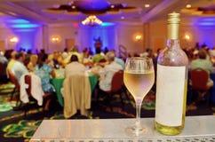 瓶和杯在桌上的白葡萄酒 免版税库存照片