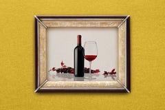 瓶和杯在画框的酒在墙壁上 免版税库存图片
