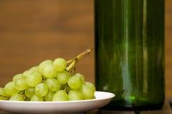 瓶和葡萄在板材 免版税库存照片