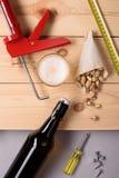 瓶啤酒、开心果和工作工具在木板条 平的位置,顶视图 库存图片
