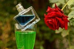 瓶在一块玻璃的香水与在红色玫瑰附近的一份饮料 库存照片