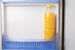 瓶在冰箱门的新鲜的橙汁 图库摄影