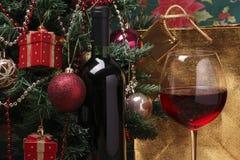 瓶在和圣诞树的红葡萄酒 库存图片