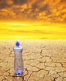 瓶在干燥破裂的土壤的水在日落 免版税库存照片