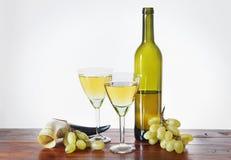 瓶在木桌上的酒和葡萄束 免版税库存图片