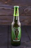 瓶在木背景的海涅肯啤酒 免版税库存照片