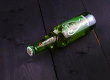 瓶在木背景的海涅肯啤酒 库存图片