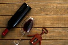 瓶在木背景的酒和杯子拔塞螺旋 与拷贝空间的顶视图 免版税库存图片