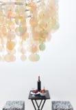 瓶在桌上的红葡萄酒,美丽的枝形吊灯装饰的a 图库摄影