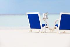 瓶在椅子之间的香宾在美丽的海滩 库存照片