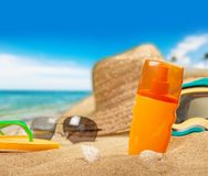 瓶在沙滩的遮光剂化妆水 免版税库存照片