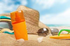 瓶在沙滩的遮光剂化妆水 免版税库存图片