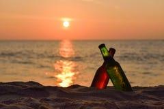 瓶在海滩的啤酒在日落 免版税库存图片