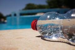 瓶在游泳池边的水 免版税库存图片