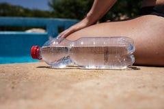 瓶在游泳池边的水 免版税库存照片
