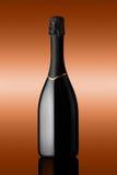 瓶在被镀青铜的背景的汽酒 库存图片