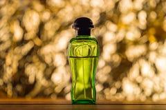 瓶在金黄bokeh的香水点燃背景 正面图 免版税库存图片
