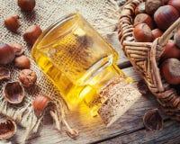 瓶坚果油和篮子用欧洲榛树在老厨房用桌上 免版税库存照片